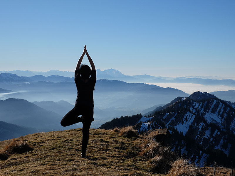 A woman who's learning to love herself again doing yoga on a mountaintop.