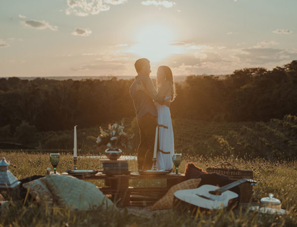 A man who used one of these ideas for romantic things to do standing on top of a hill at sunset with his happy girlfriend.