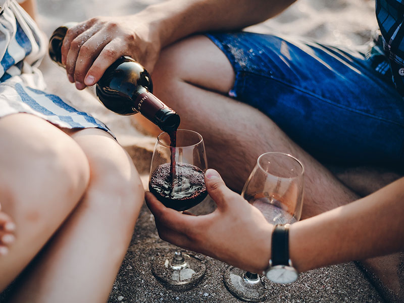 A couple coming up with things to talk about on a second date while pouring wine on the beach.