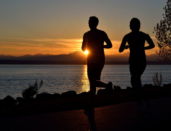 A couple who listened to these dating tips for runners, running at sunset together.