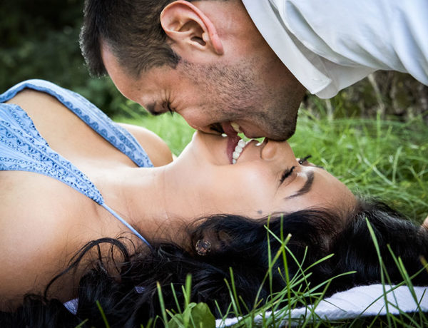 A guy who took these best first date tips for men kissing his date in the grass.