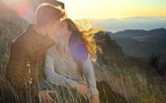 A couple who paid attention to these signs you're in love kissing on top of a mountain at sunset.