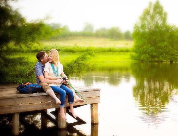 A man who's dating an extrovert as an introvert, fishing with his girlfriend on a dock and laughing.