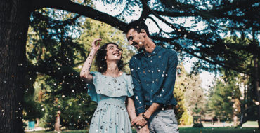 A woman who learned how men fall in love, smiling with her husband under a tree at their wedding.