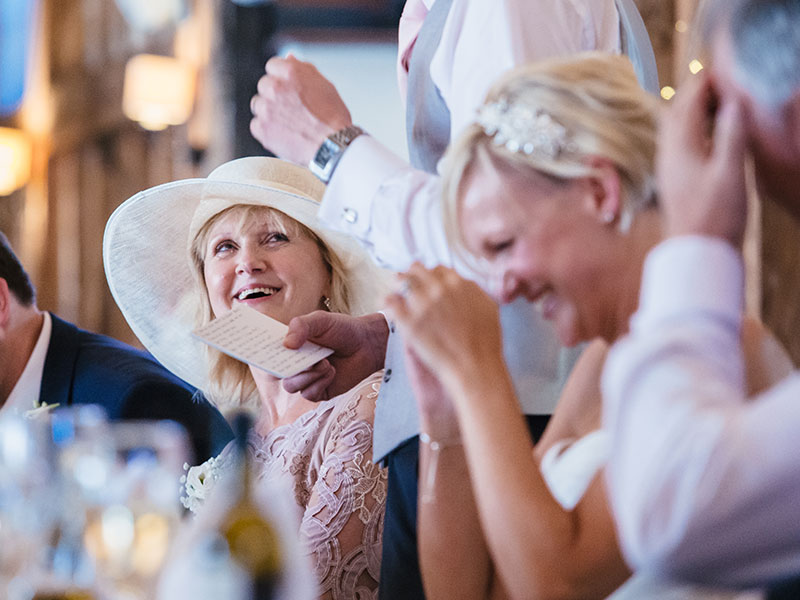A crowd at a wedding laughing after the maid of honor speech.