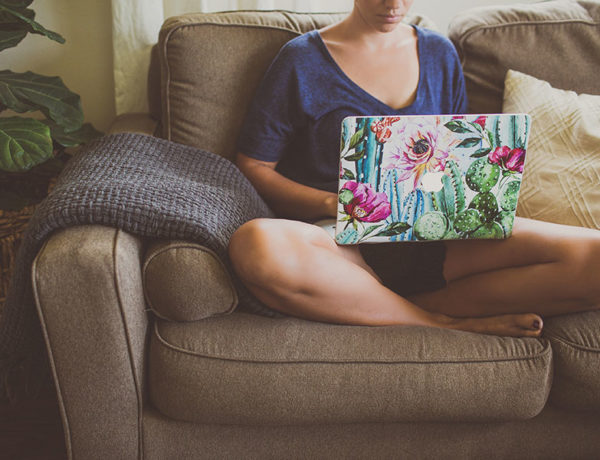 A woman who learned how to write an online dating profile, writing on her computer on the couch.