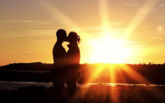 A couple standing in front of a sunset, sharing a kiss on a first date.