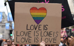 A group of people holding up a sign that says love is love is love is love at a Pride parade.