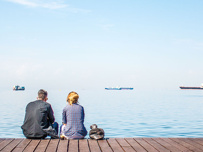A woman who learned how to tell someone you're not interested talking to a guy she's seeing while they sit on a dock.
