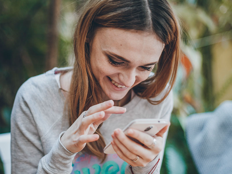 A woman sending flirty messages on her phone and laughing.