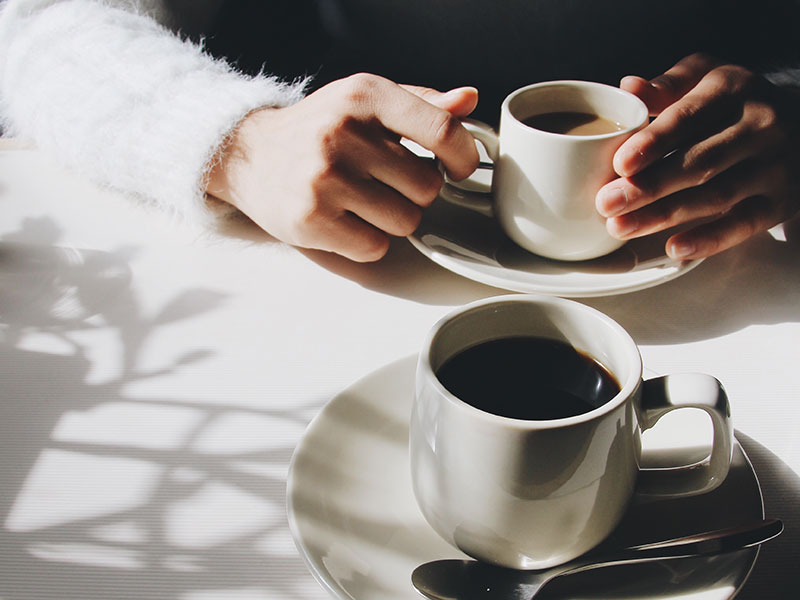 "The hands of two people having a ""I'm not interested"" talk while they hold their coffee cups at a cafe."