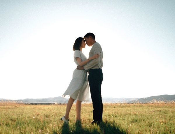 A couple who practices self-care hugging in a field.