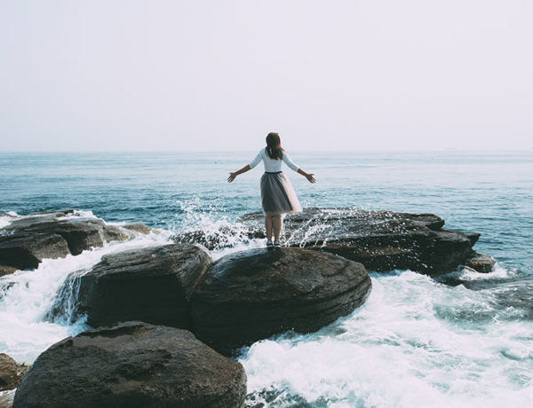 A woman who used this break up survival kit standing on a rock in front of the ocean feeling powerful.