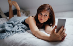 A woman in bed taking a picture of herself to send along with a goodnight quote.