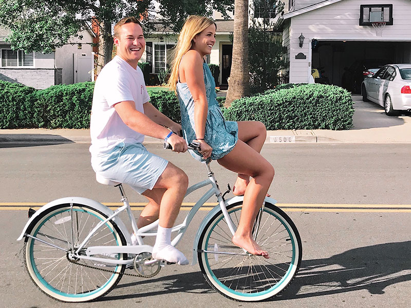 A woman riding a bike with her dating wondering about what the definition of exclusive dating vs a relationship is.