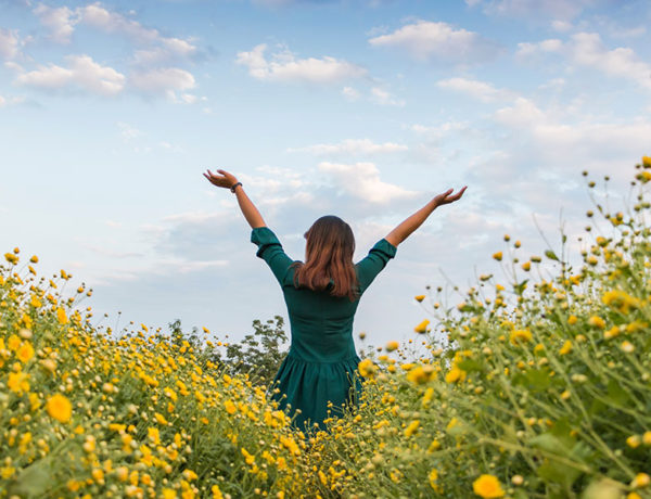A woman who took these moving forward quotes to heart standing in a field of flowers with her arms raised towards the sky.