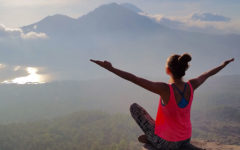 A women who's letting go of anger sitting on a mountaintop embracing the air.