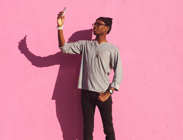 A guy standing against a pink background dating dating profile photos for his dating profile.