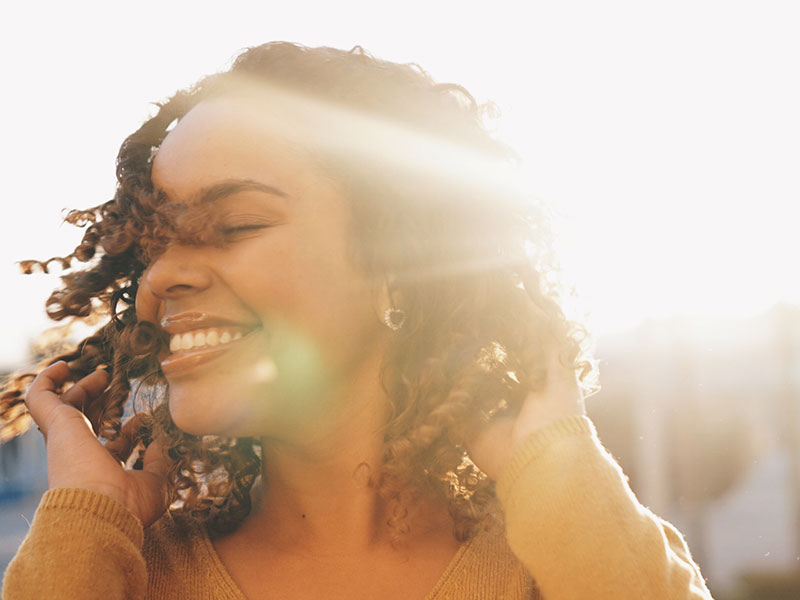 A woman smiling in the sun and enjoying her life after divorce.