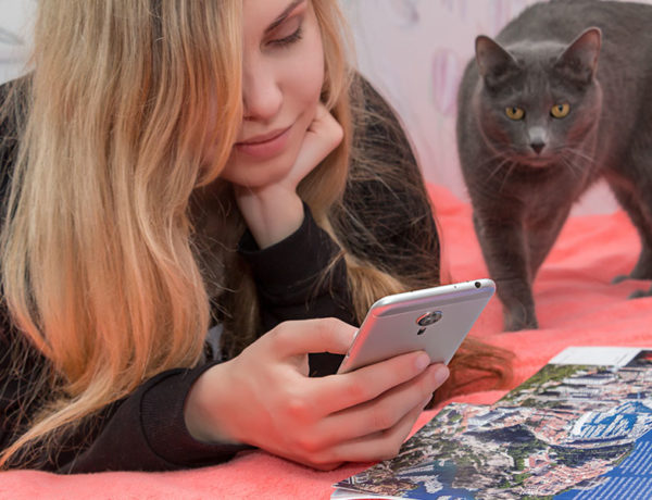 A girl looking at Tinder on her phone, trying to figure out the Tinder algorithm as her cat looks over her shoulder.