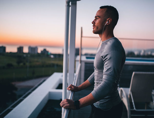 A man who's working on personal growth after a breakup looking out at the sunset at the end of his run.