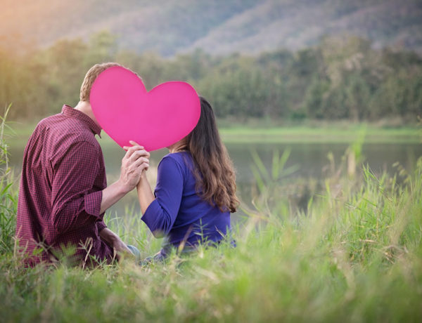 A couple getting creative in how to show affection by kissing behind a pink heart in a field.