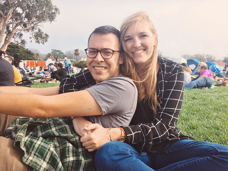 A couple dating in San Francisco at Dolores park hugging.