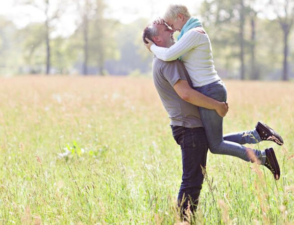 A couple dating after 50 hugging in a field and smiling.
