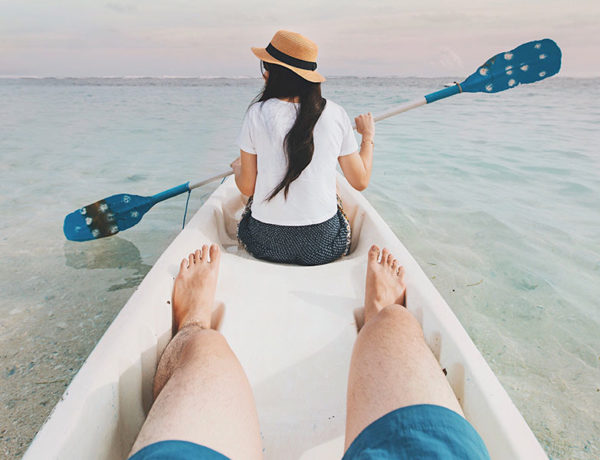 A couple using one of these fun date ideas and canoeing on the ocean together.