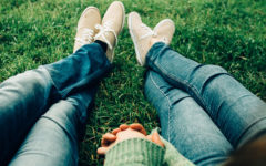 A couple holding hands in the grass while taking part in one of these bonding activities for couples.