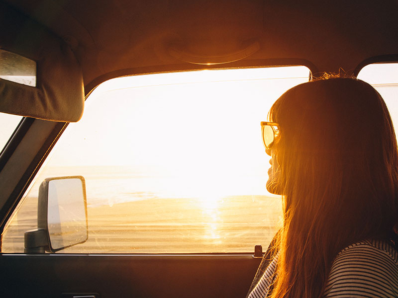 A women who is letting go of someone you love, in a car looking out the window at sunset on an open road.