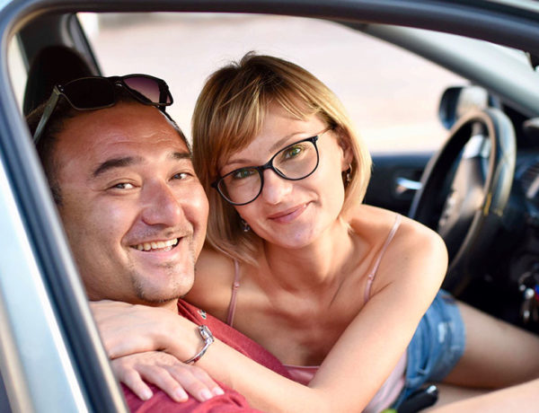 A woman who listened to this relationship advice for women, smiling and hugging her boyfriend in the car.