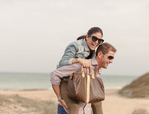 An older women dating a younger man getting a piggy back ride from her boyfriend and laughing on the beach.