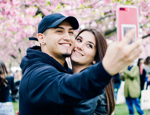 A man who said to himself, I need a girlfriend, smiling with his new girlfriend while they take a selfie at the park.