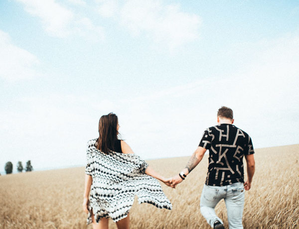 A couple walking in a field, holding hands. One of them has a fear of intimacy.
