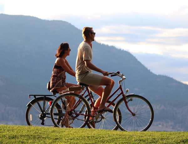A couple riding bikes together on their fourth date, laughing and having a conversation while they look at the view.