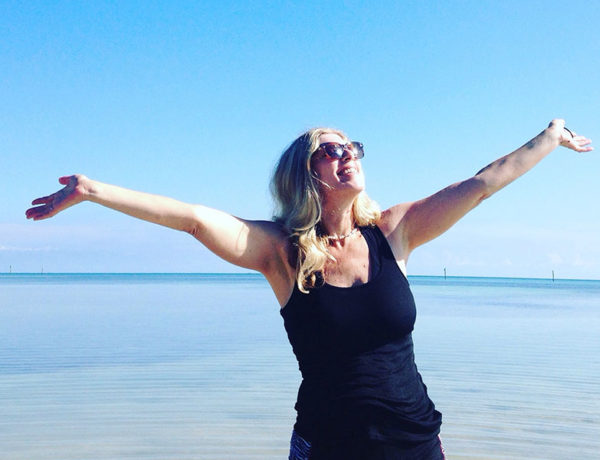 A woman who listened to these breakup tips at the beach with her arms out, embracing life because she's getting over it.