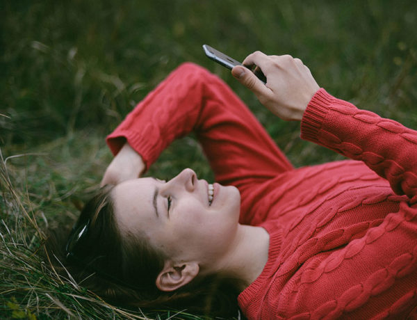 A woman in the grass looking at a dating app on her phone, using some of these digital dating tips.