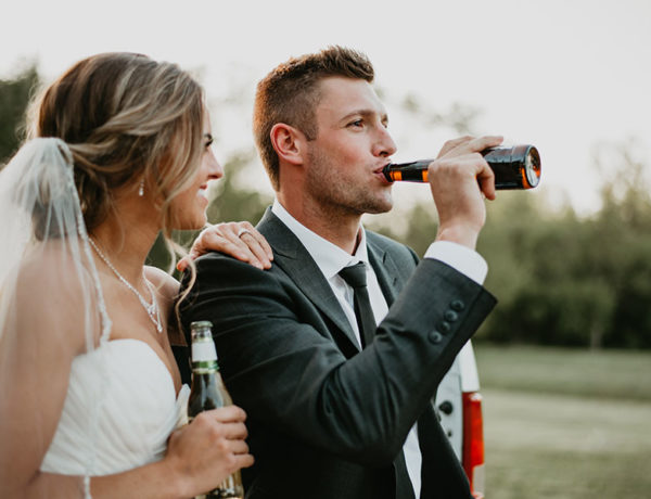A happy couple drinking beer at their wedding because they know these questions to ask before getting married.