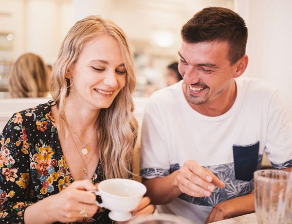 A couple chatting and laughing over coffee as they establish good communication in their relationship.