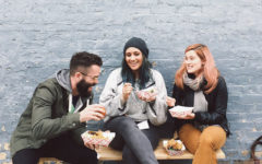 A woman and her new boyfriend meeting her friend as they all laugh and talk over lunch.