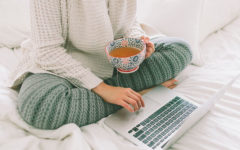 A woman using these dating profile tips to update her online dating profile while she's in bed drinking coffee.