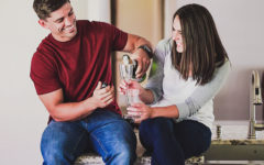 A couple who used these fun things for couples to do laughing and clinking champagne glasses as they have a home date night.
