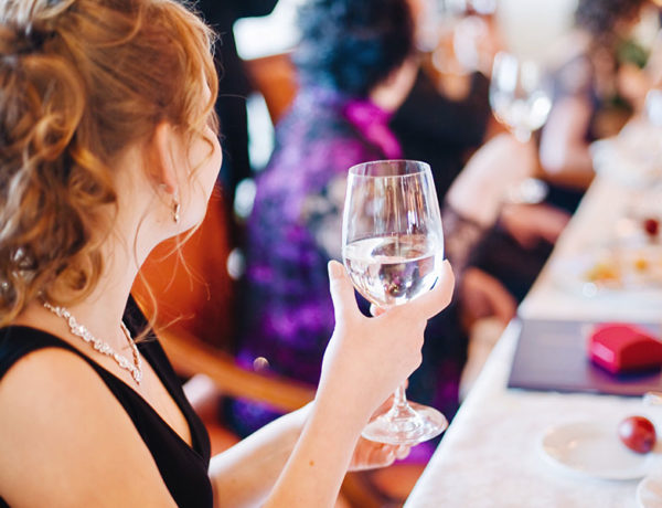 A guest at a wedding holding her glass of water looking around the room for someone to flirt with.