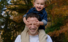 A single dad laughing as he holds his son on his shoulders.