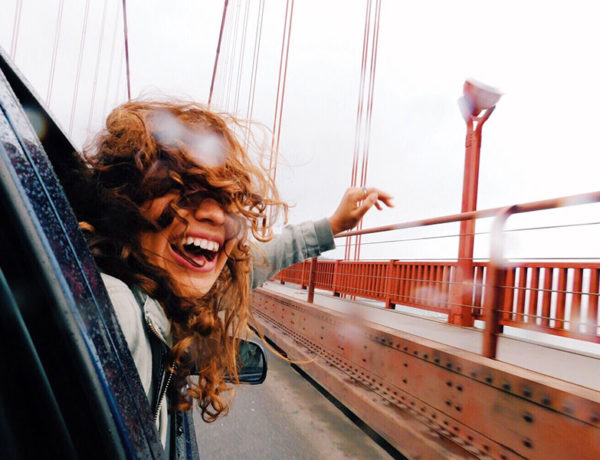 A woman who's letting go of someone, hanging out a car door window with a smile as she goes over a bridge and moves on with her life.