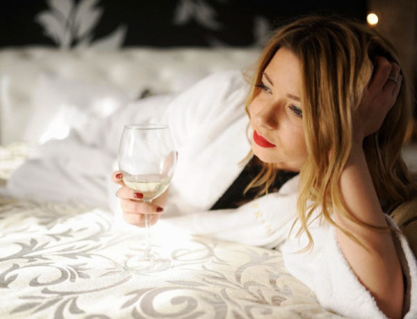 A woman who's comfortable being single smiling to herself in bed with a glass of wine.