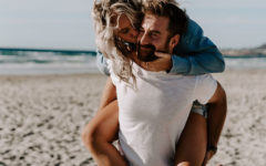 A woman who figured out what single men want, laughing and kissing her boyfriend's cheek on the beach.