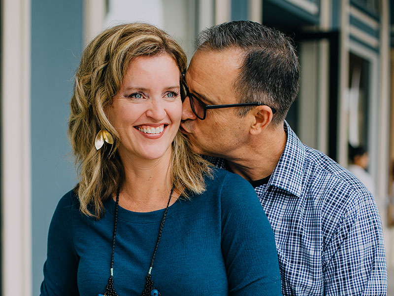 A woman who learned what men over 50 are attracted to, smiling as she gets a kiss on the cheek from her boyfriend.