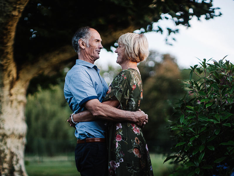 A couple dating after 50, smiling and hugging while looking into each other's eyes.